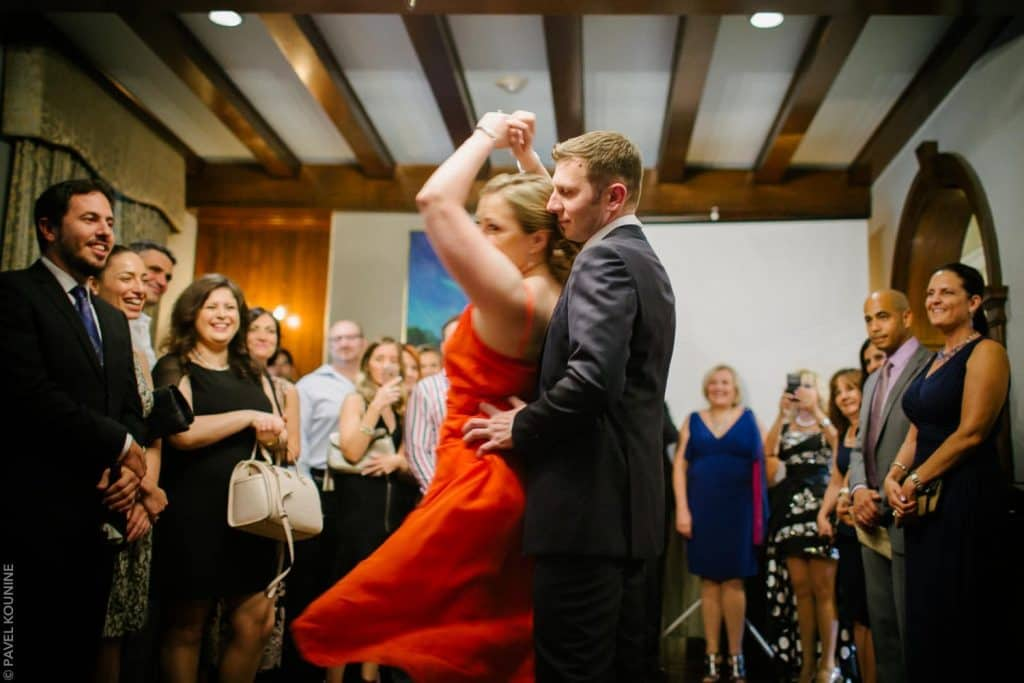 Photojournalistic wedding photography first dance is a tango with bride in bright red dress.
