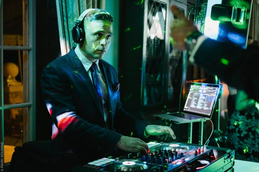 Photojournalistic wedding photography, dj playing dance music is bathed in green light.