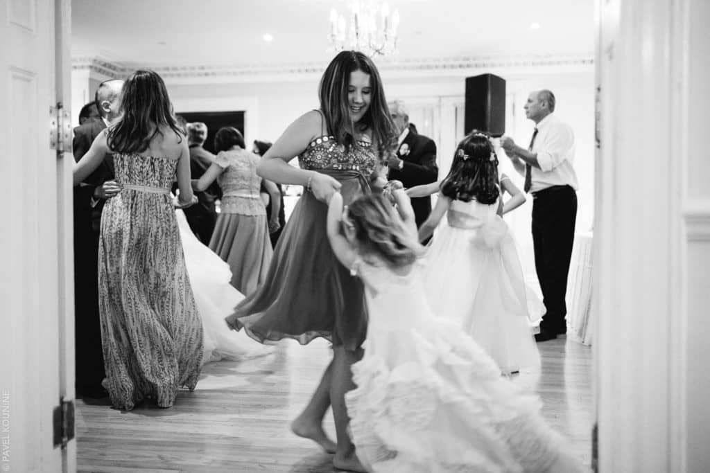 Photojournalistic wedding photography dance, a little girl being swung by a teenage girl on the dance floor.