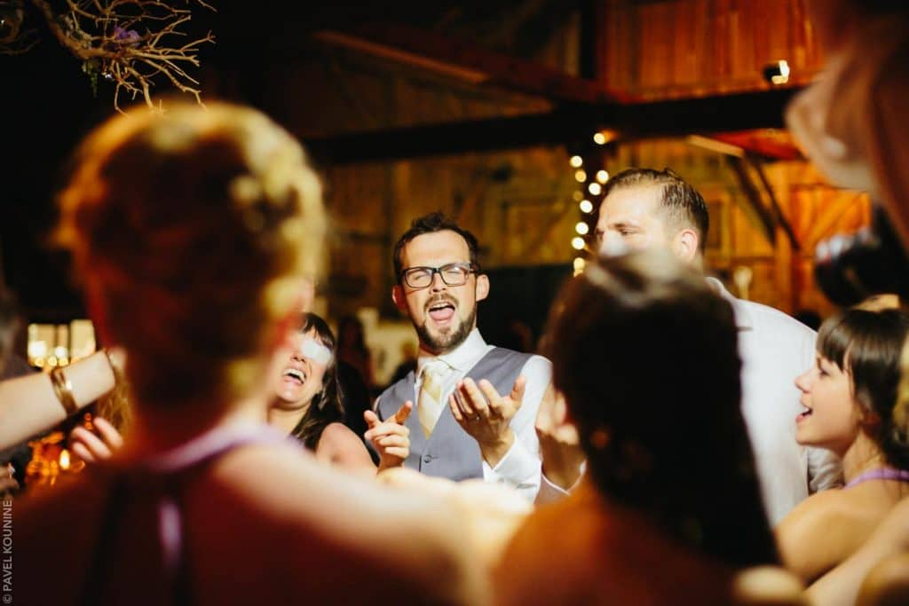 Groom and guests singing songs in a circle.