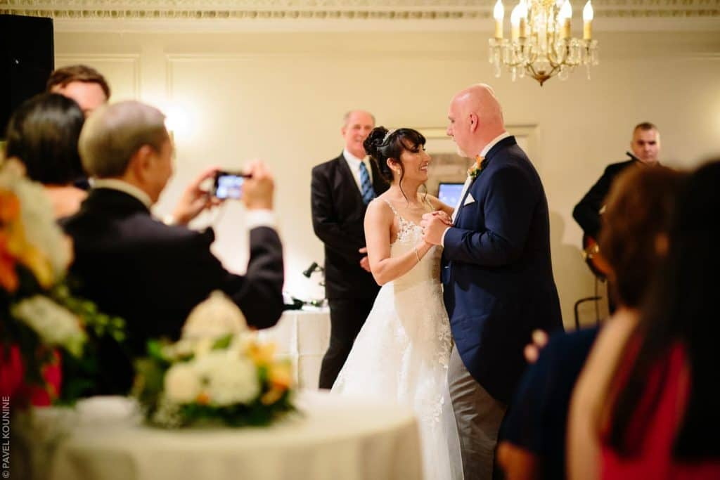 The bride and groom share first dance at Paletta Mansion with guests watching.