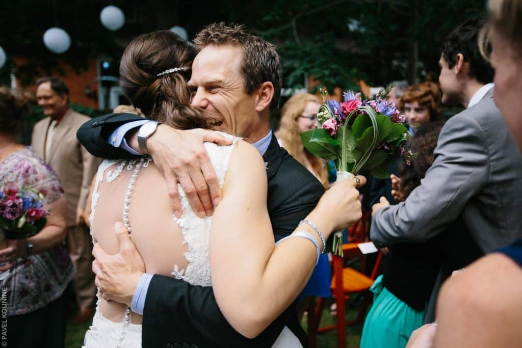 Guest hugs bride during receiving line after ceremony.