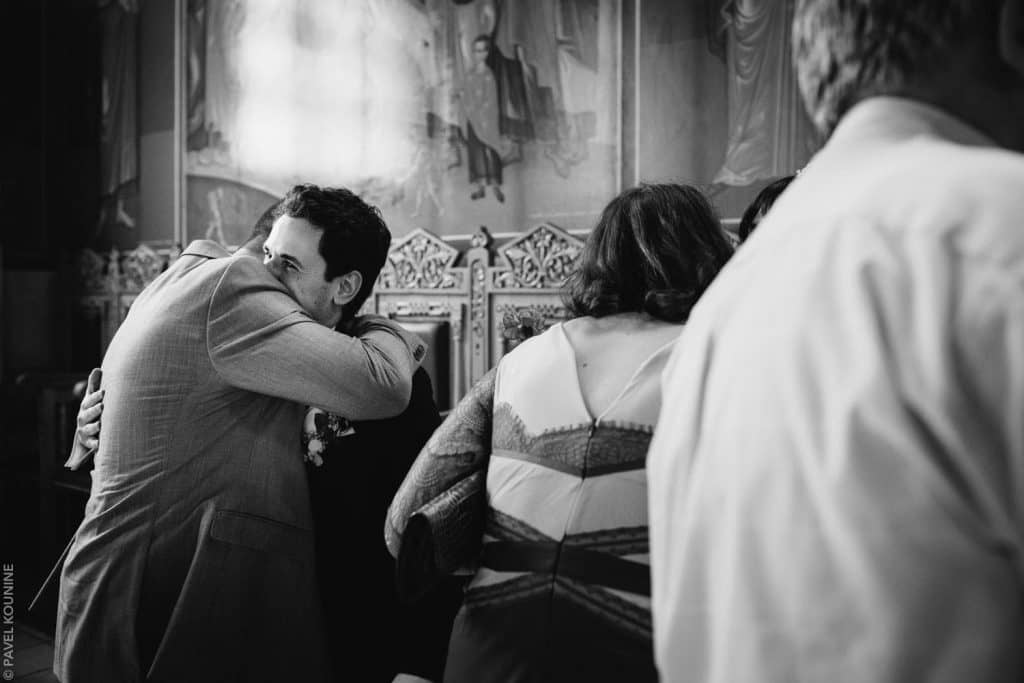 Guest hugs groom during receiving line after ceremony.