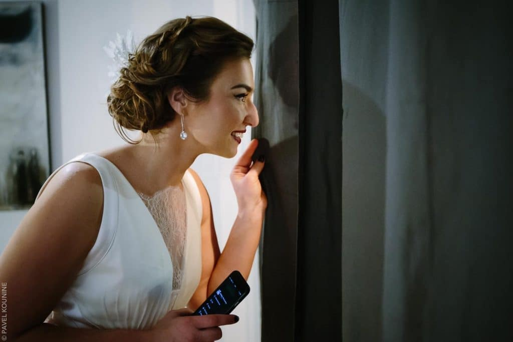 The bride peeks out through a curtain at her guests.