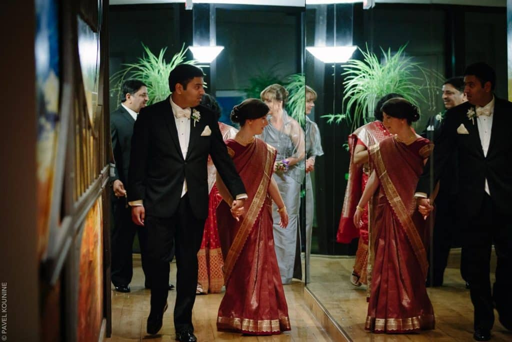 Bride and groom walking down a hall of mirrors with the bride checking out her red sari in the mirror.