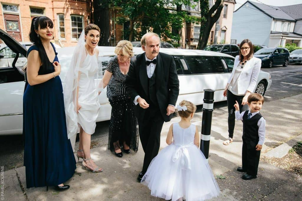 Surprised bride with family after arriving by limo.