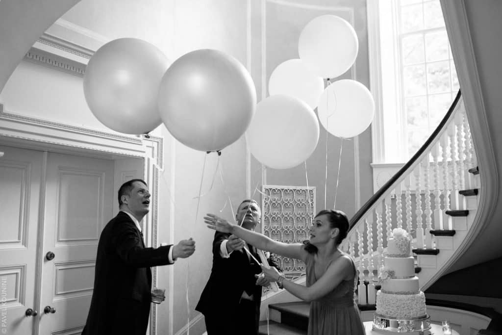Photojournalistic wedding photography of three people sorting helium balloons.
