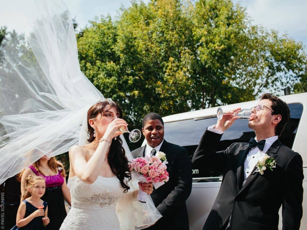 Bride and groom drinking sparkling wine by the limo.