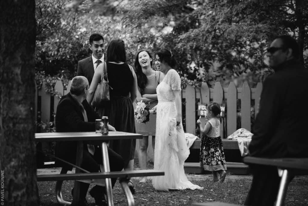 Photojournalistic wedding photography of bride talking with guests after ceremony.
