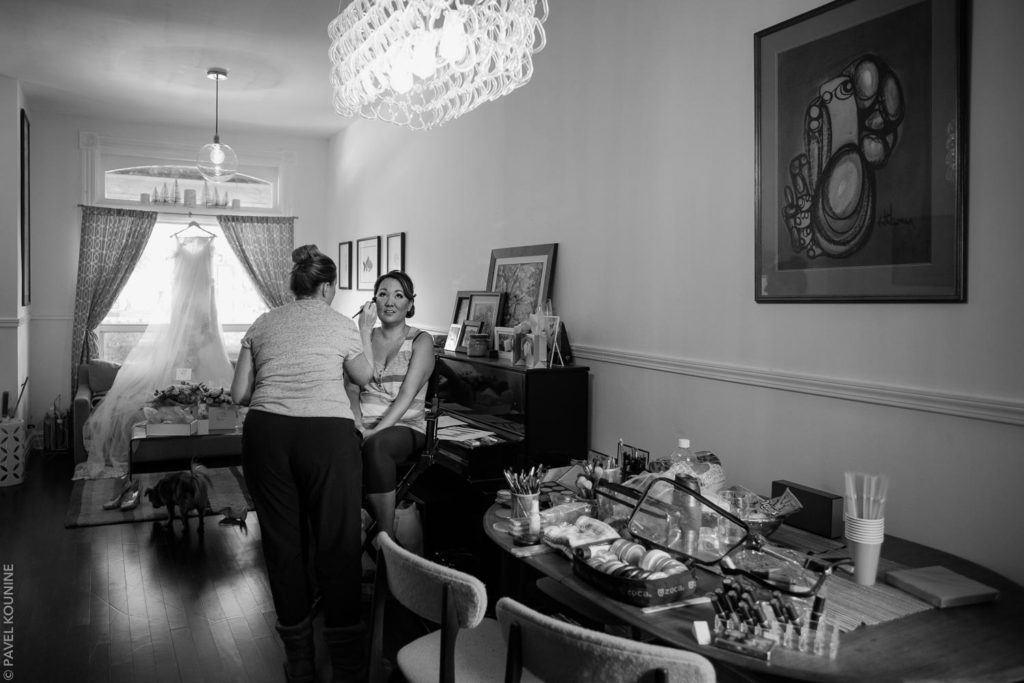 The bride is getting her makeup done in her living room.
