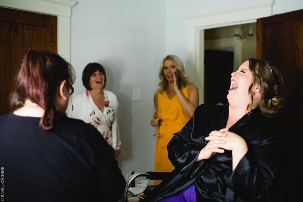 The bride laughs in the makeup chair.