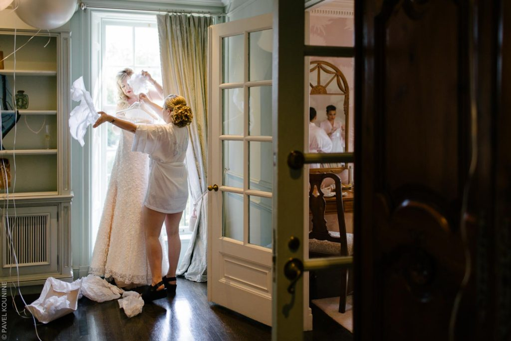 The bride and mother remove padding from the wedding dress to hang it up by the window.