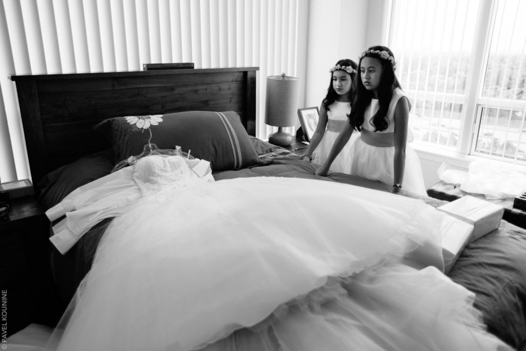 Two flower girls examine the wedding dress resting on a bed.