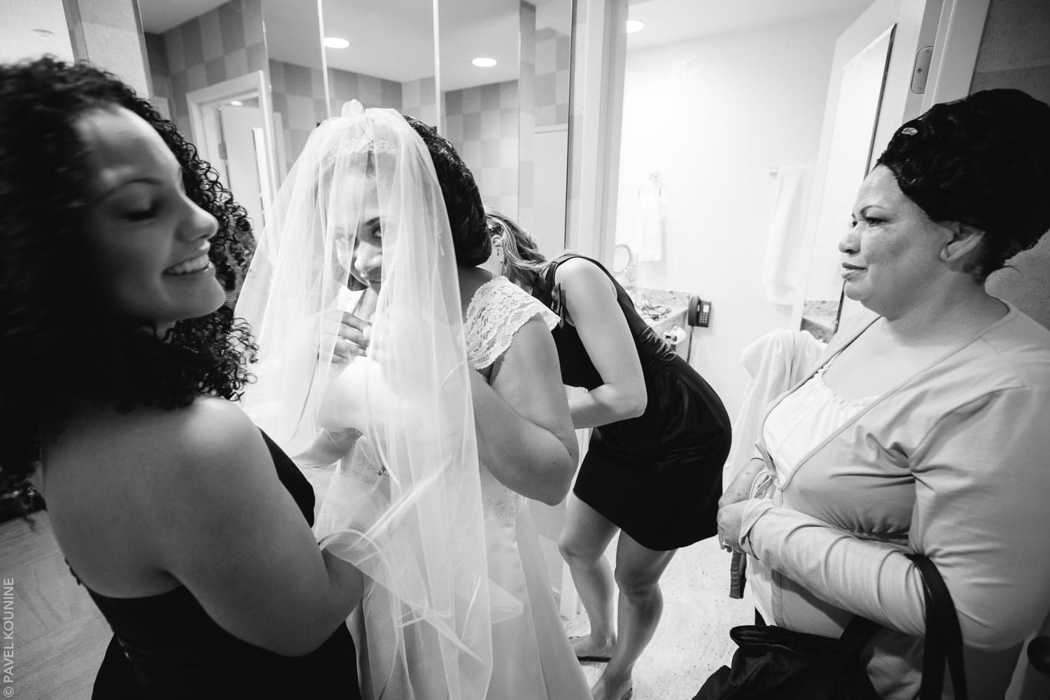 The bride is helped into her wedding dress in the hotel room.