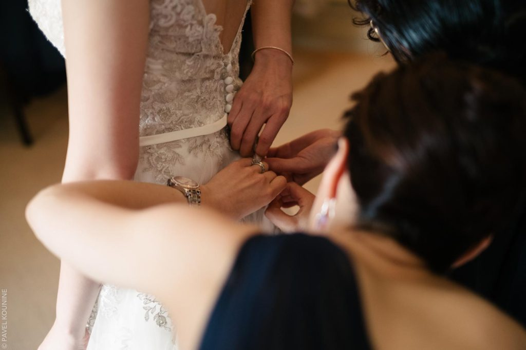 Several hands doing up the buttons on bride's wedding dress.