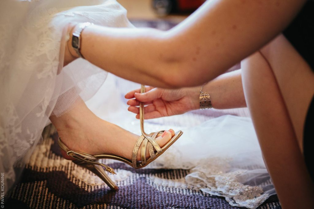 Bride's friend assists her with putting on the shoes.