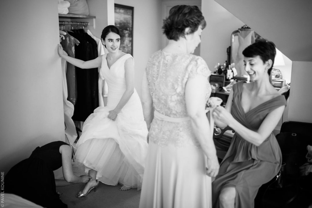 Bride in big wedding dress gets help with putting on her shoes.