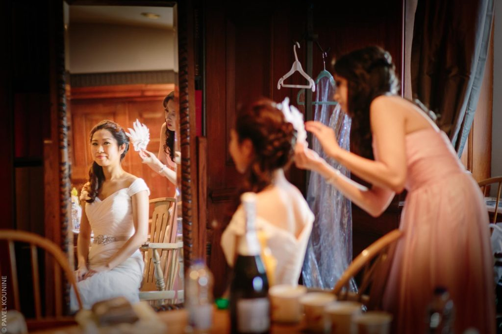 Woman helps bride with final touches to her hair.