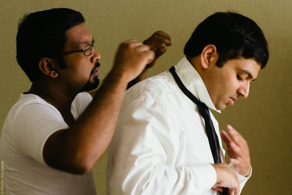 The groom gets help with his tie.