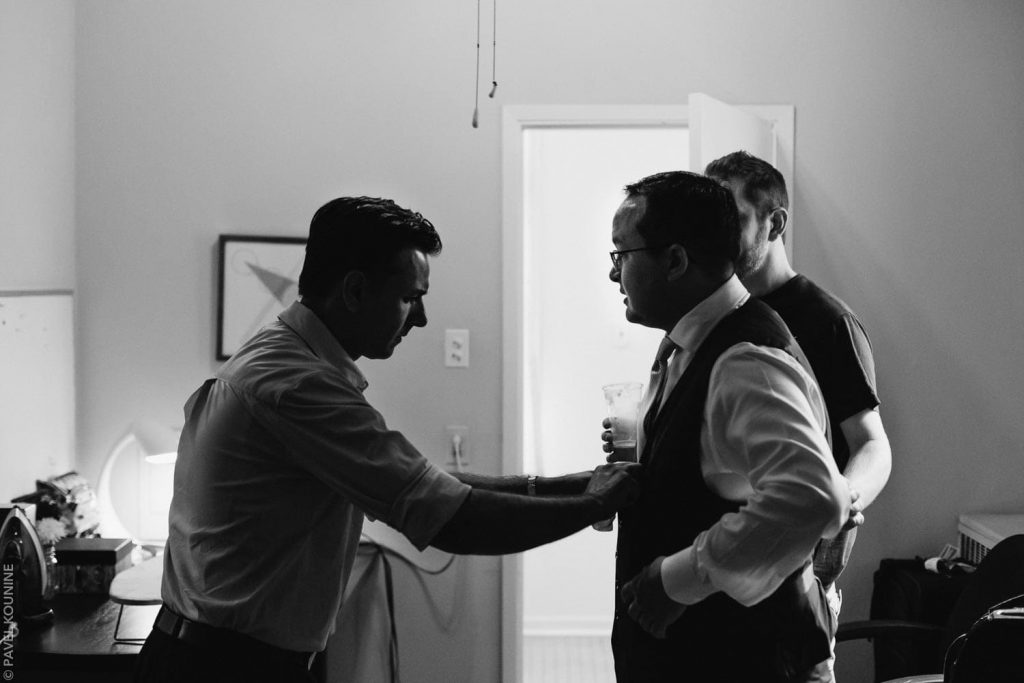 Silhouette of best man helping groom with shirt buttons.