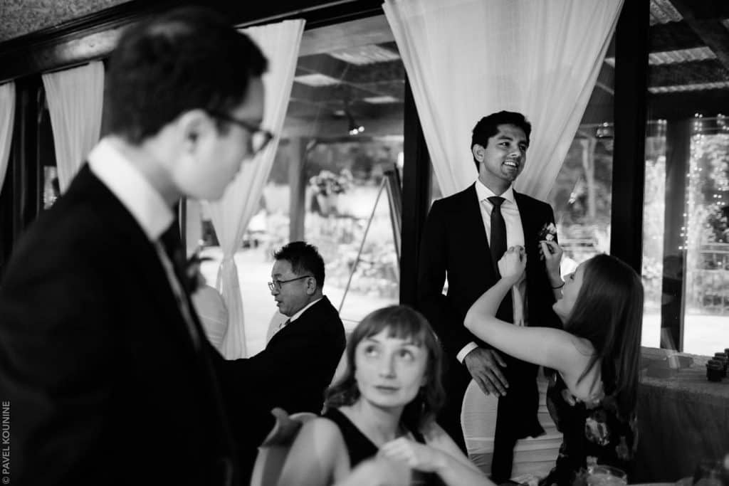 A woman adjusts the boutonniere on the best man.