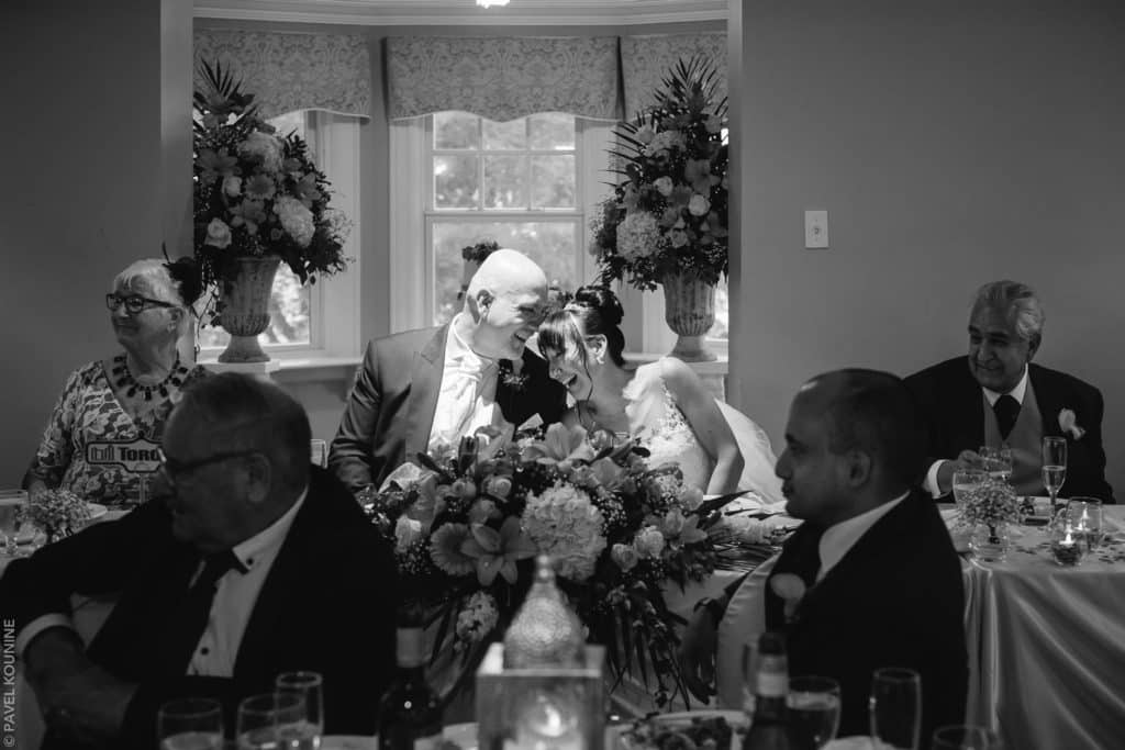 Bride and groom share a laugh during a speech at the dinner reception at Paletta Mansion in Burlington.