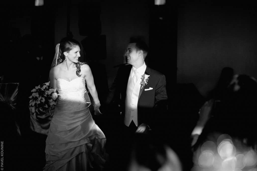 Bride and groom walking through a beam of sunlight towards their dinner table.