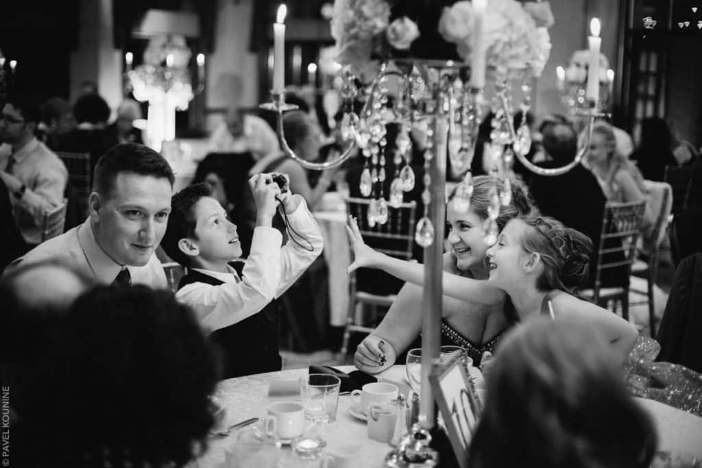 A boy takes a photo of his friends at the dinner reception.
