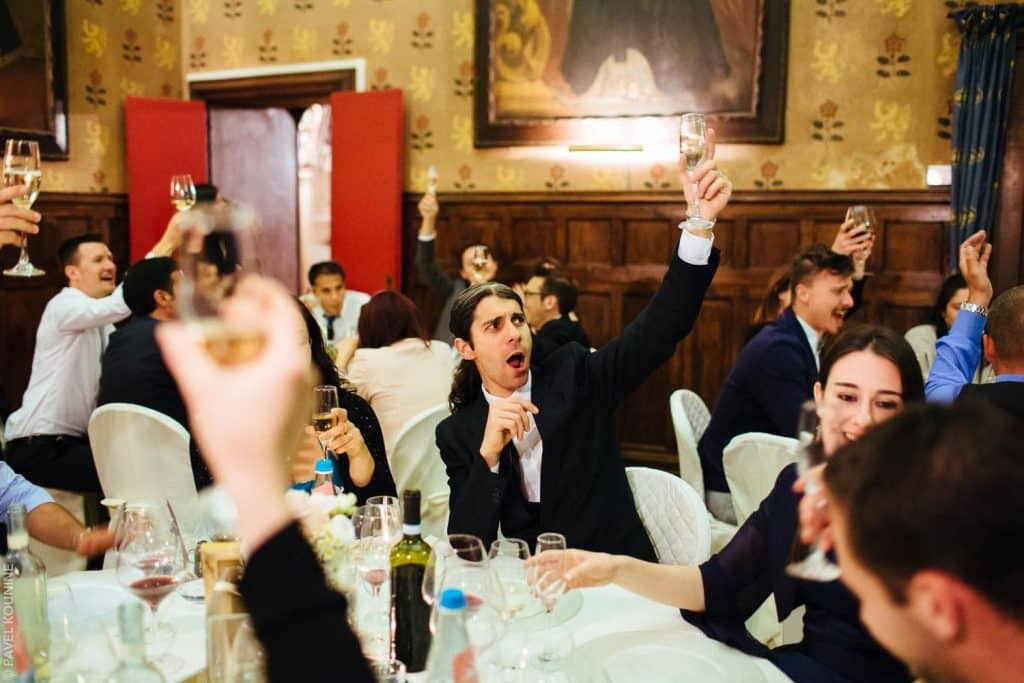 Guests raising their glasses to toast the bride and groom at reception inside an old Italian castle.
