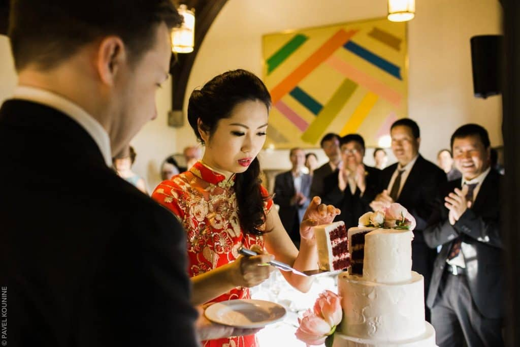 Chinese bride in traditional red dress cutting the cake for groom.