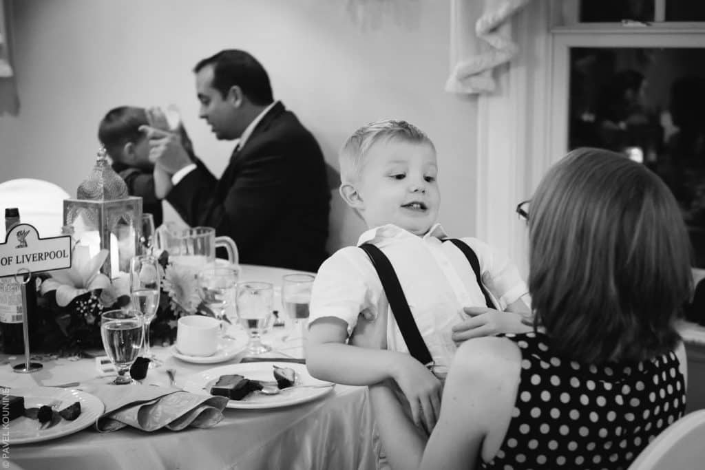 A boy makes a funny face at the woman holding him during wedding dinner reception.