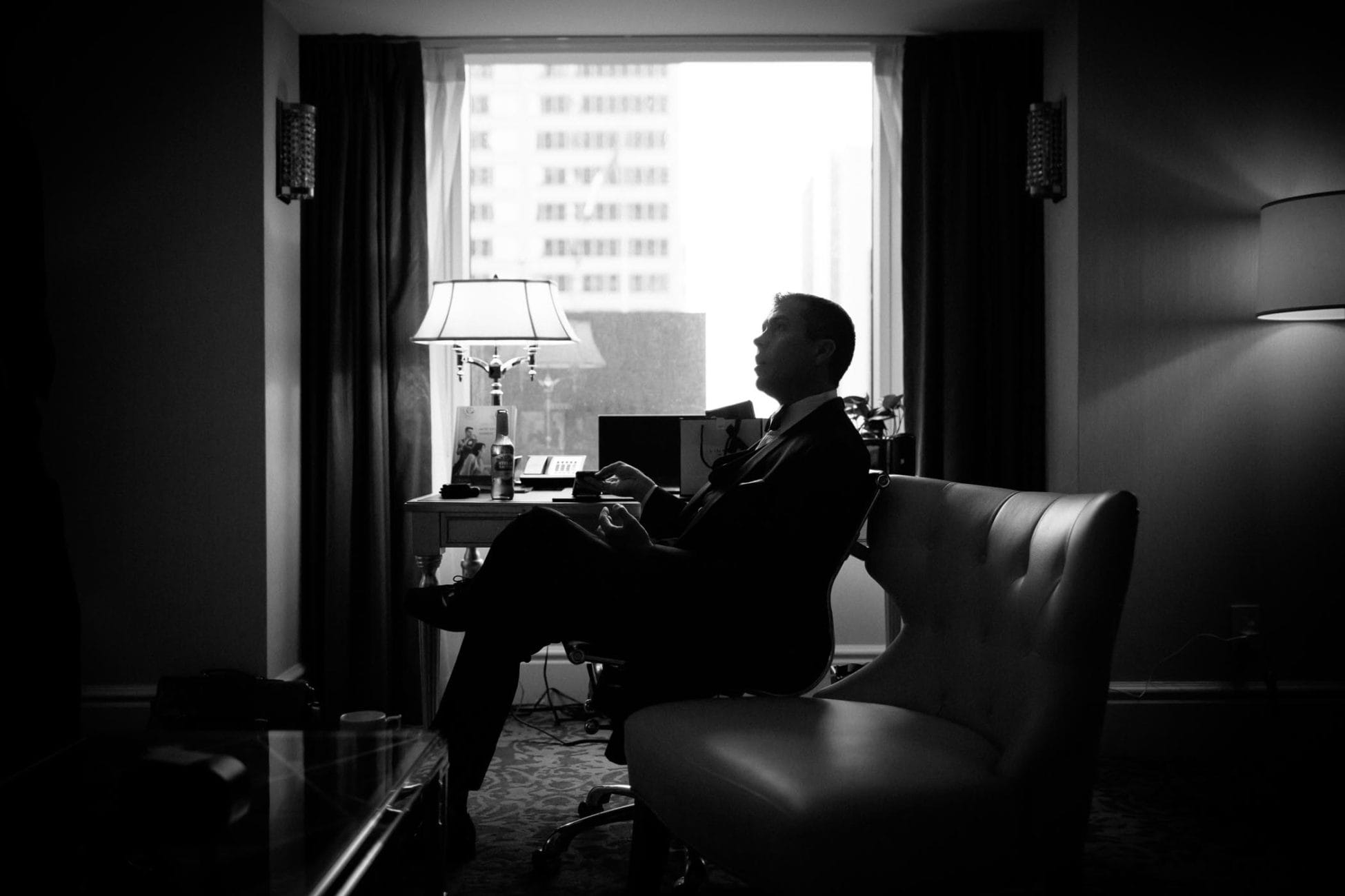 A silhouette of the groom against large square window of Trump Hotel wedding in Toronto