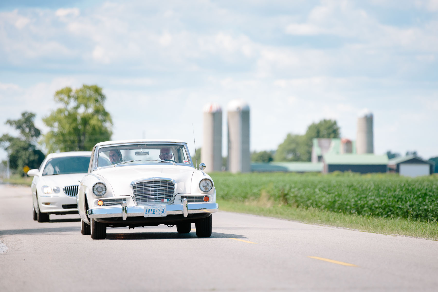 Bride and her father arriving in his white 1963 Studebaker Gran Turismo for the ceremony in this rural farm wedding.