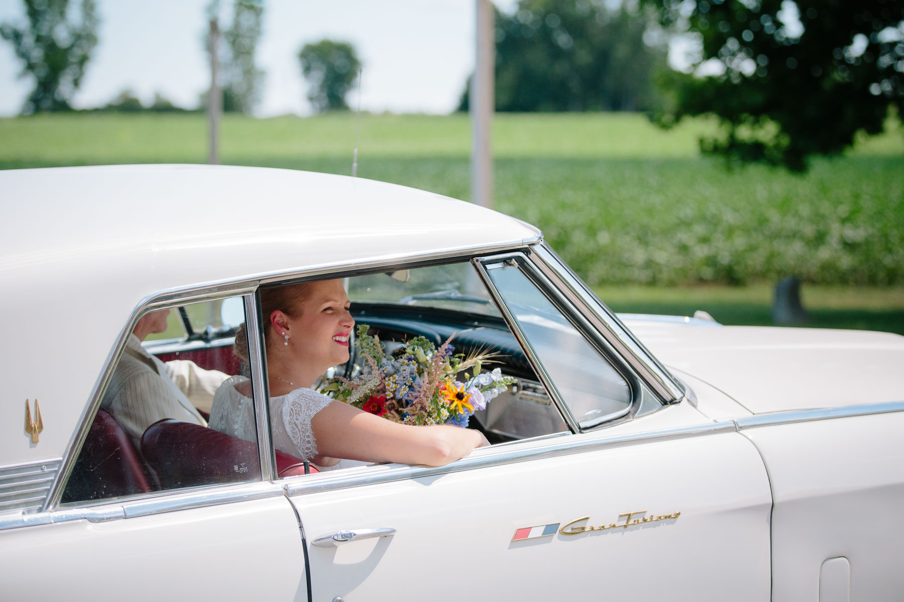 The bride looks out from the 1963 Studebaker Gran Turismo as it pulls up to the church in this rural farm wedding.