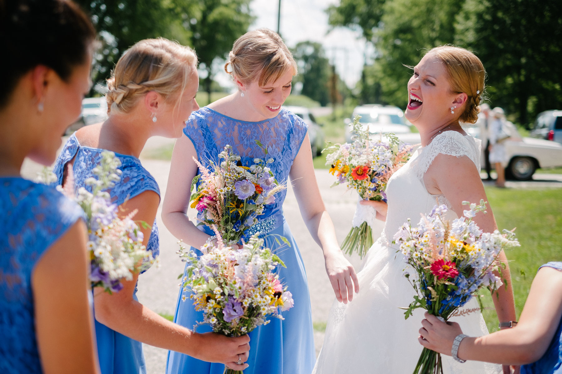 Bride laughs as bridesmaids examine her dress outside the church in this rural farm wedding.