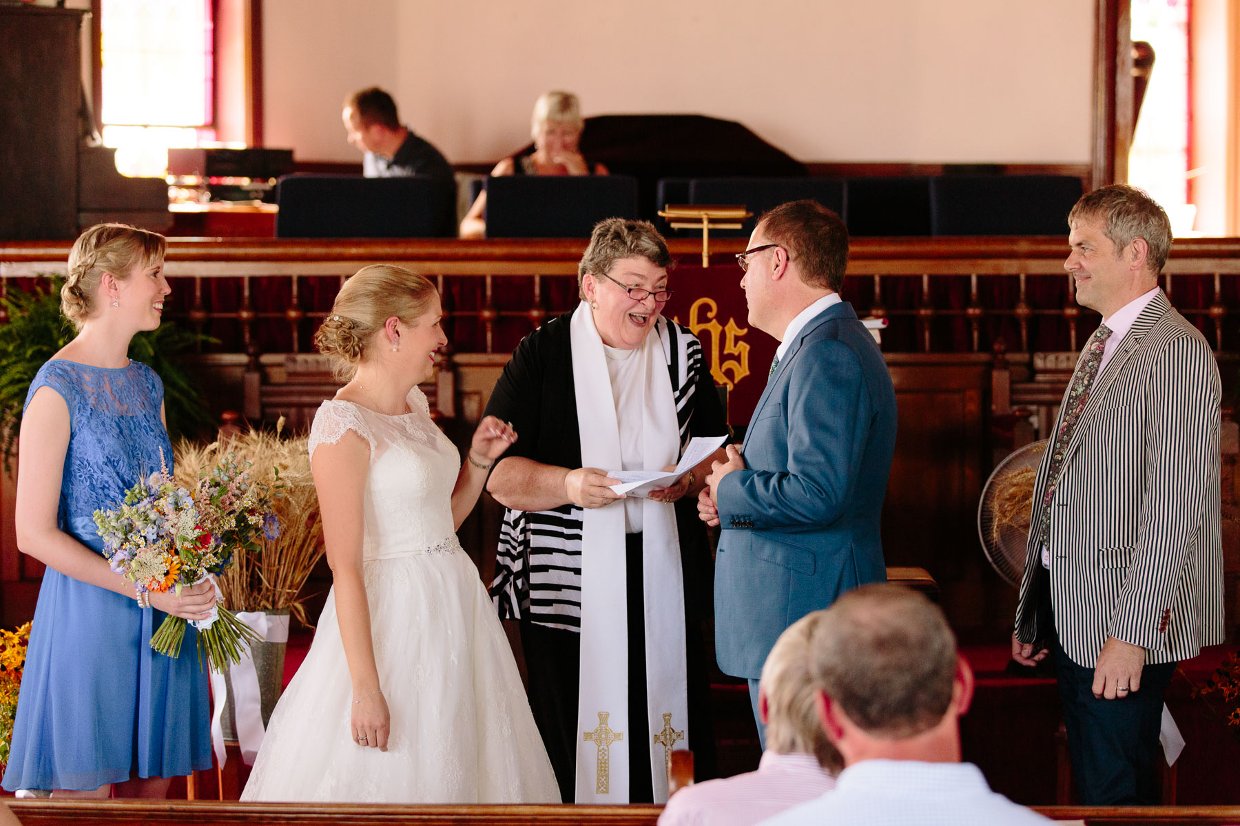 The female minister of this United Church congregation laughs with the bride and groom during ceremony at intimate rural wedding.