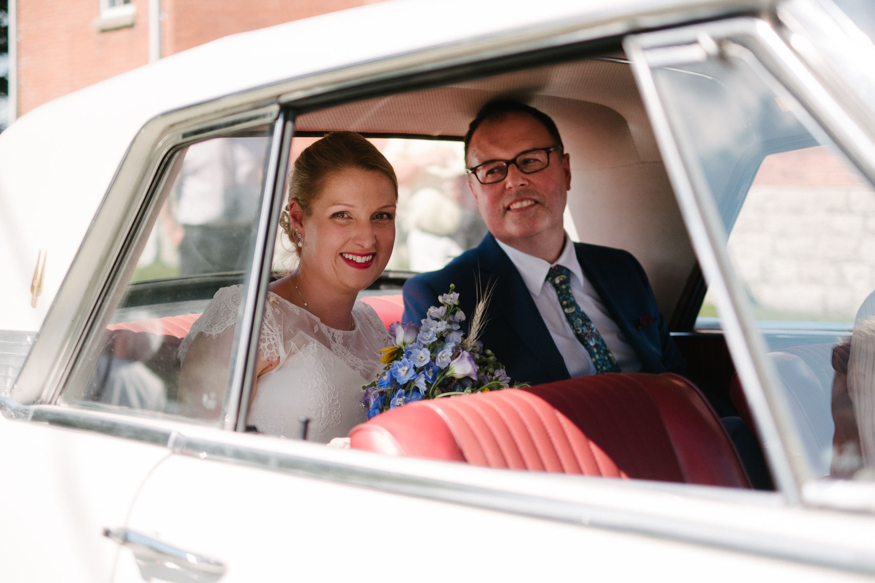 Bride and groom in back seat of a white Studebaker in this rustic family farm wedding.