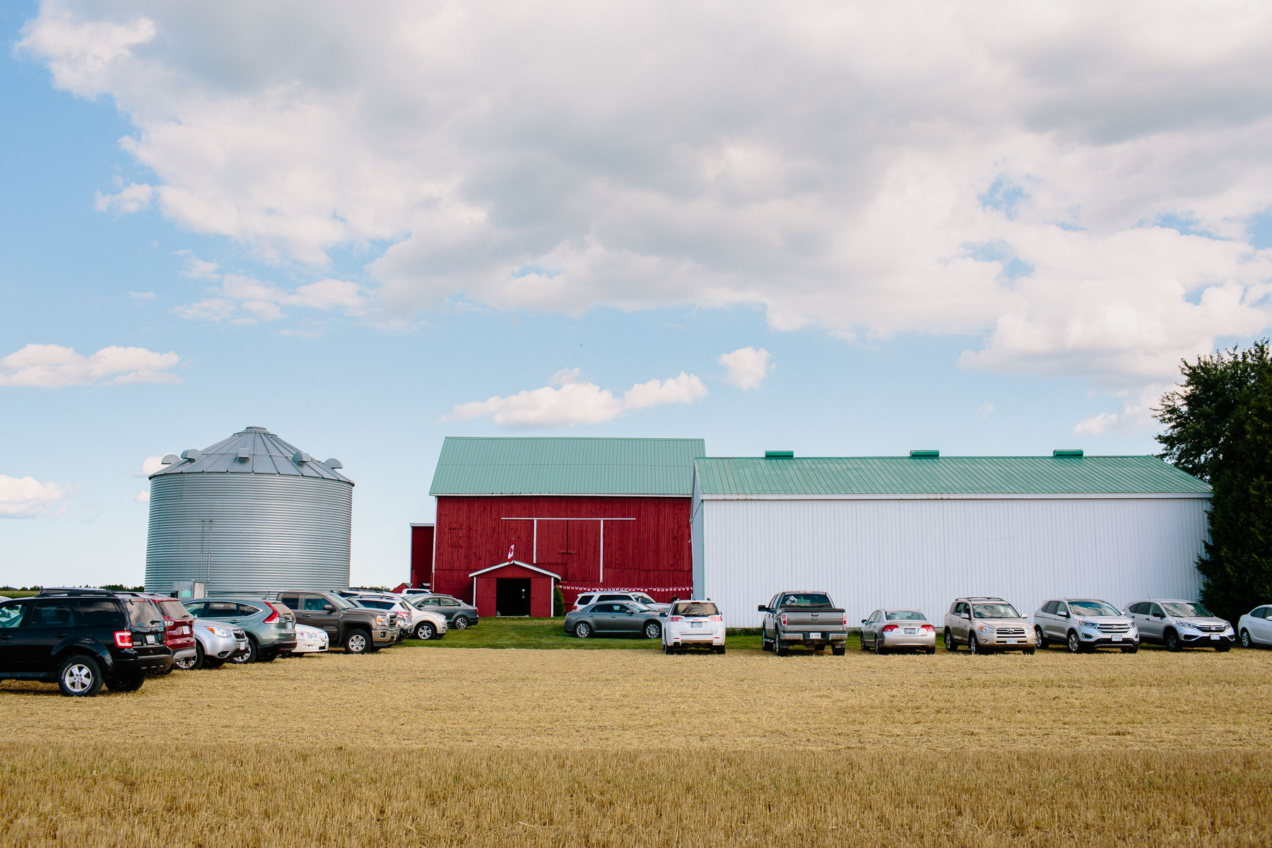 Guests cars parked on a cleared field to the side of the barns and silo at this rustic farm wedding.