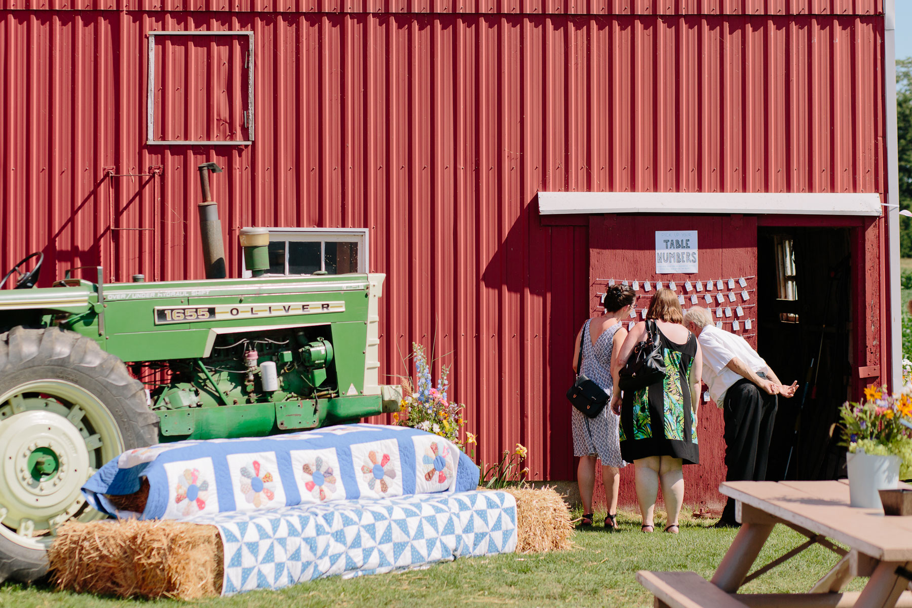Guests checking their table numbers on side of barn with old 1655 Oliver Tractor in foreground at a rustic farm wedding.