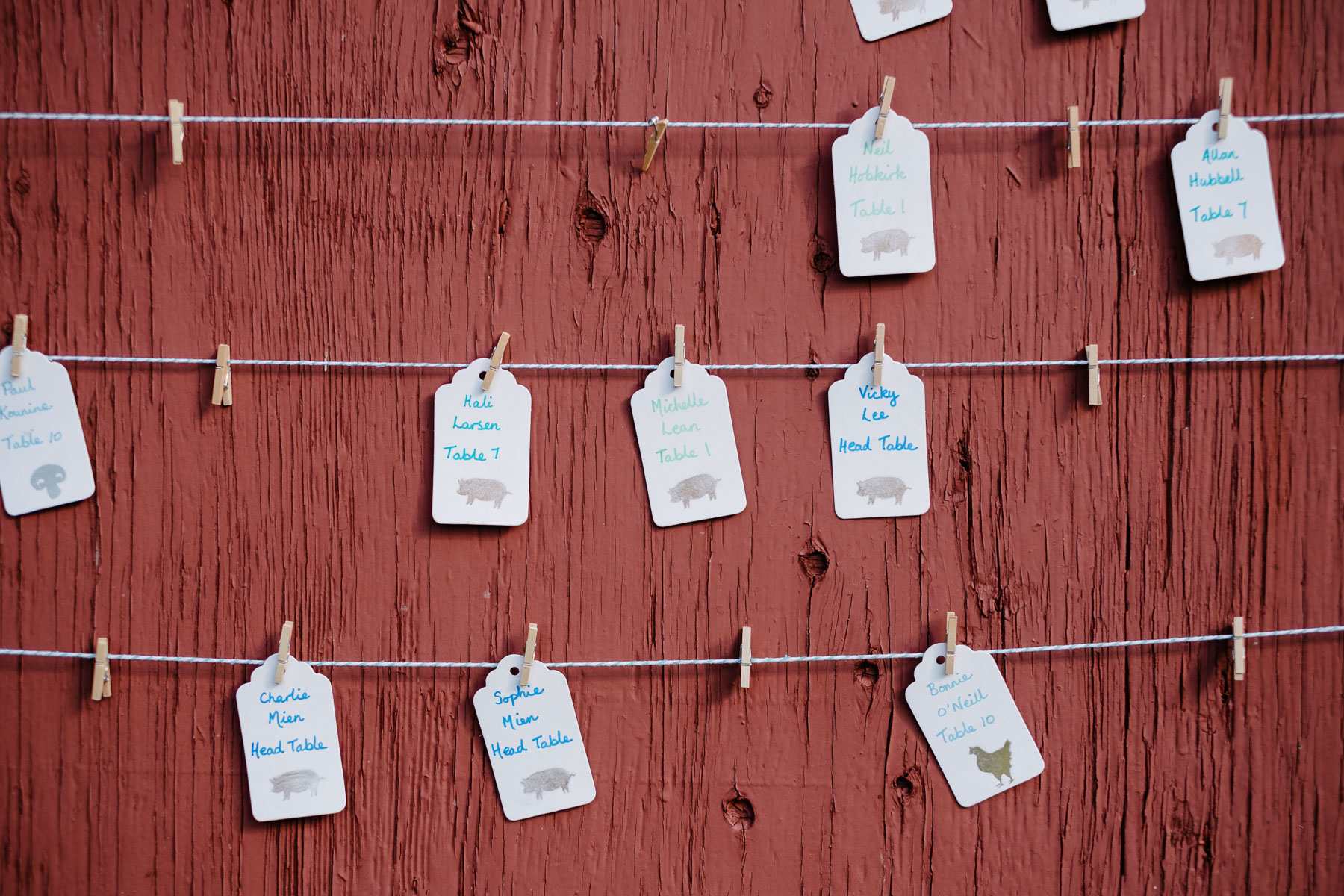 Seating assignment tags hanging on strings and clothespins at rustic farm wedding.