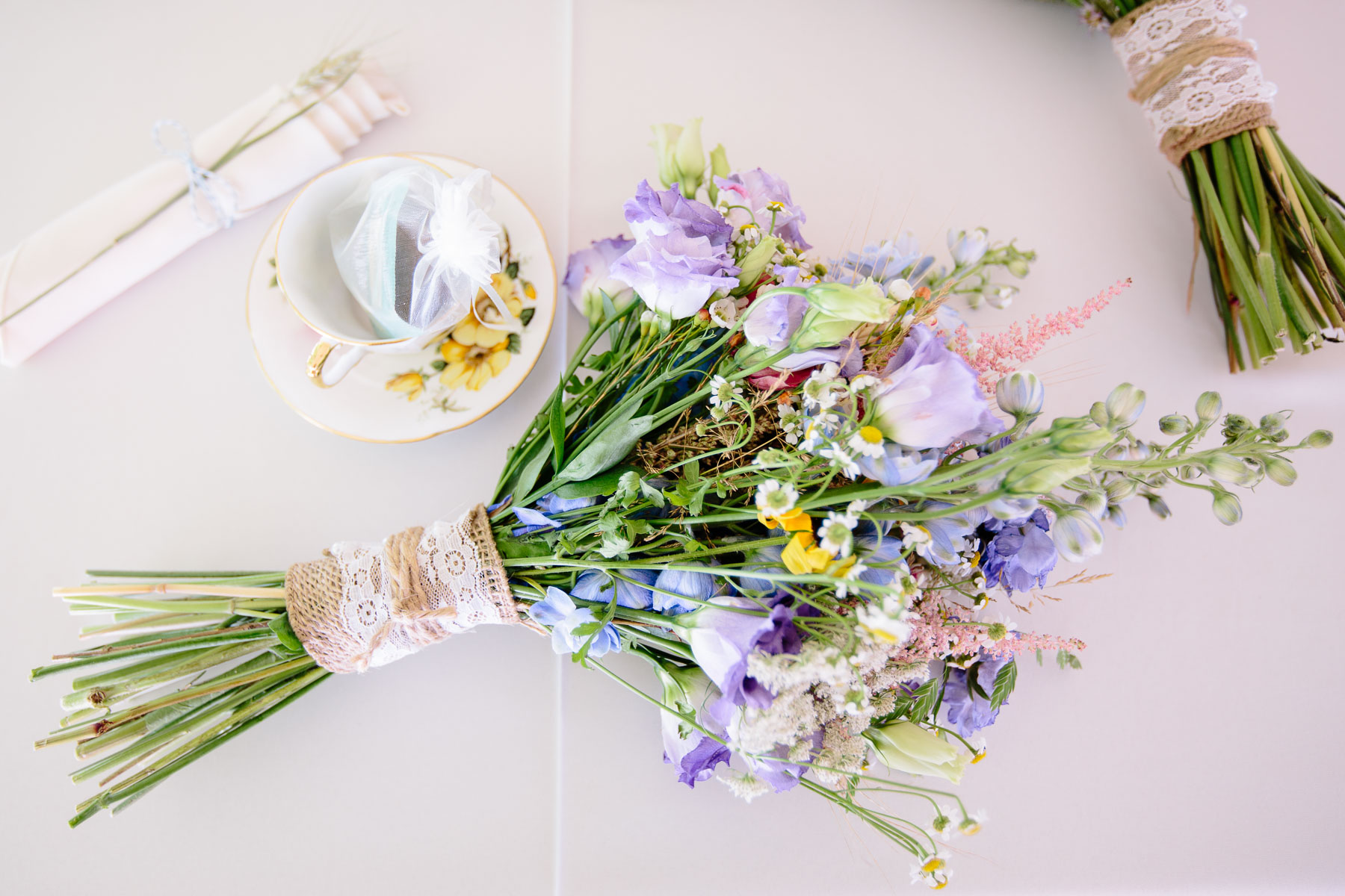 Beautiful bouquet of violet flowers and some table decorations at a rustic farm wedding.