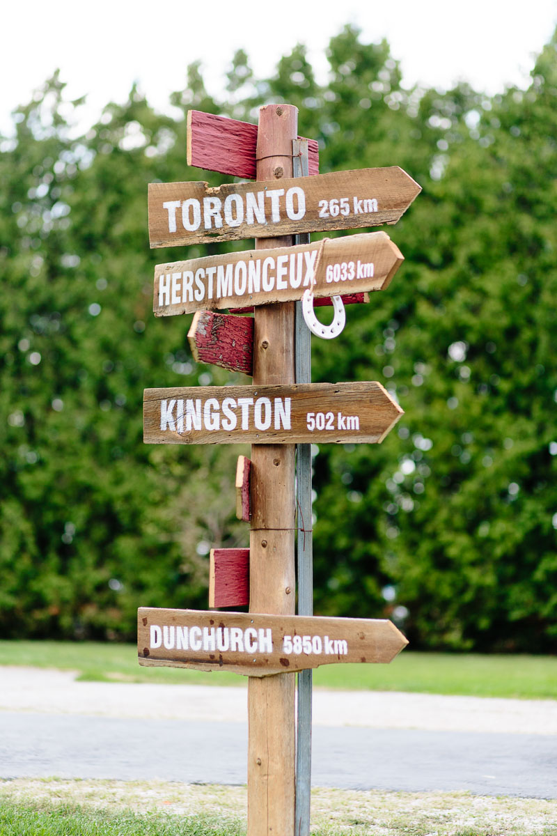 A decorative direction and distance sign indicating various cities at this rural farm wedding.