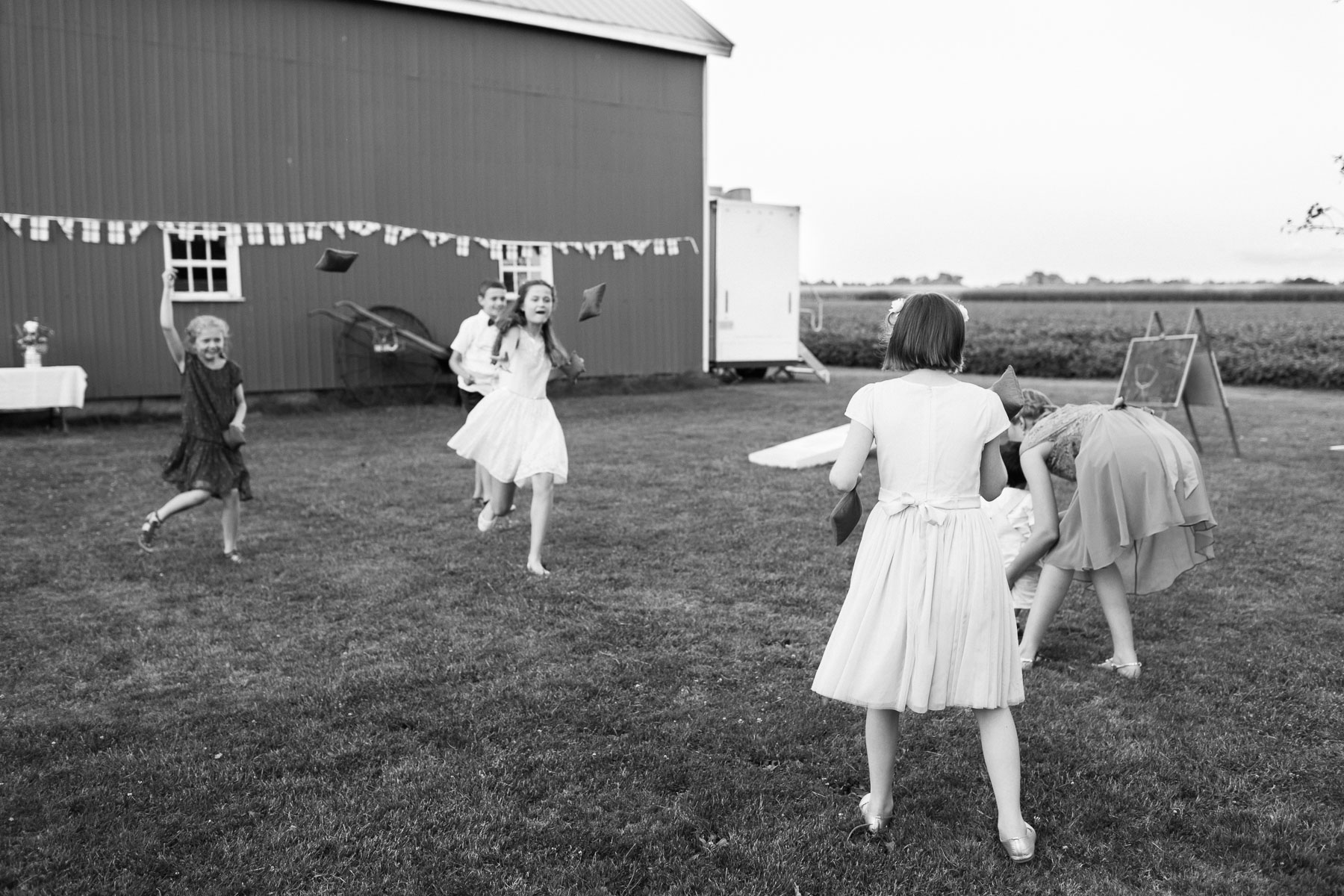 Kids throwing beanbags with barn in background at this rural farm wedding.