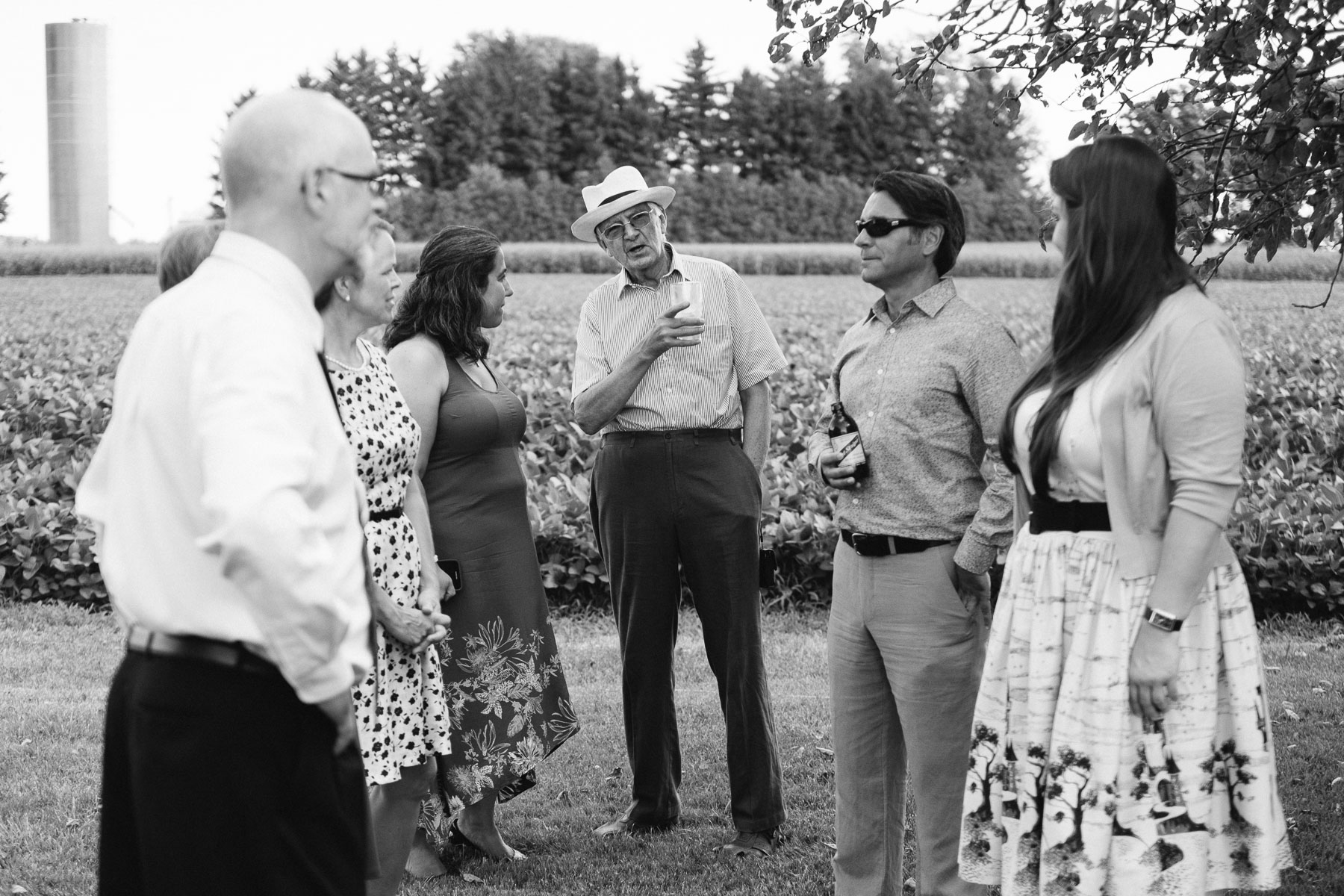 The groom's father wearing a white hat talking to several guests at a rural family farm wedding.