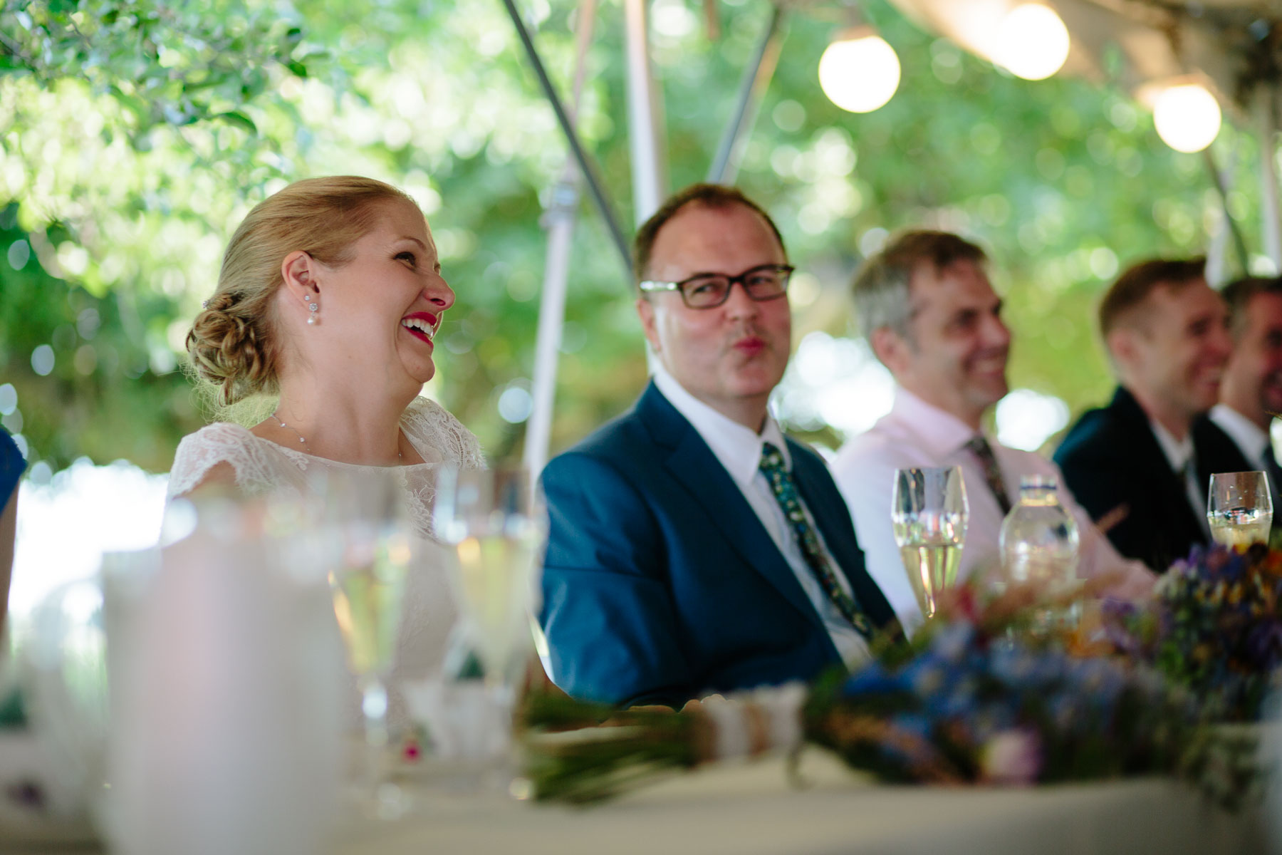 The bride laughs and the groom looks at her during a speech at a rural farm wedding.