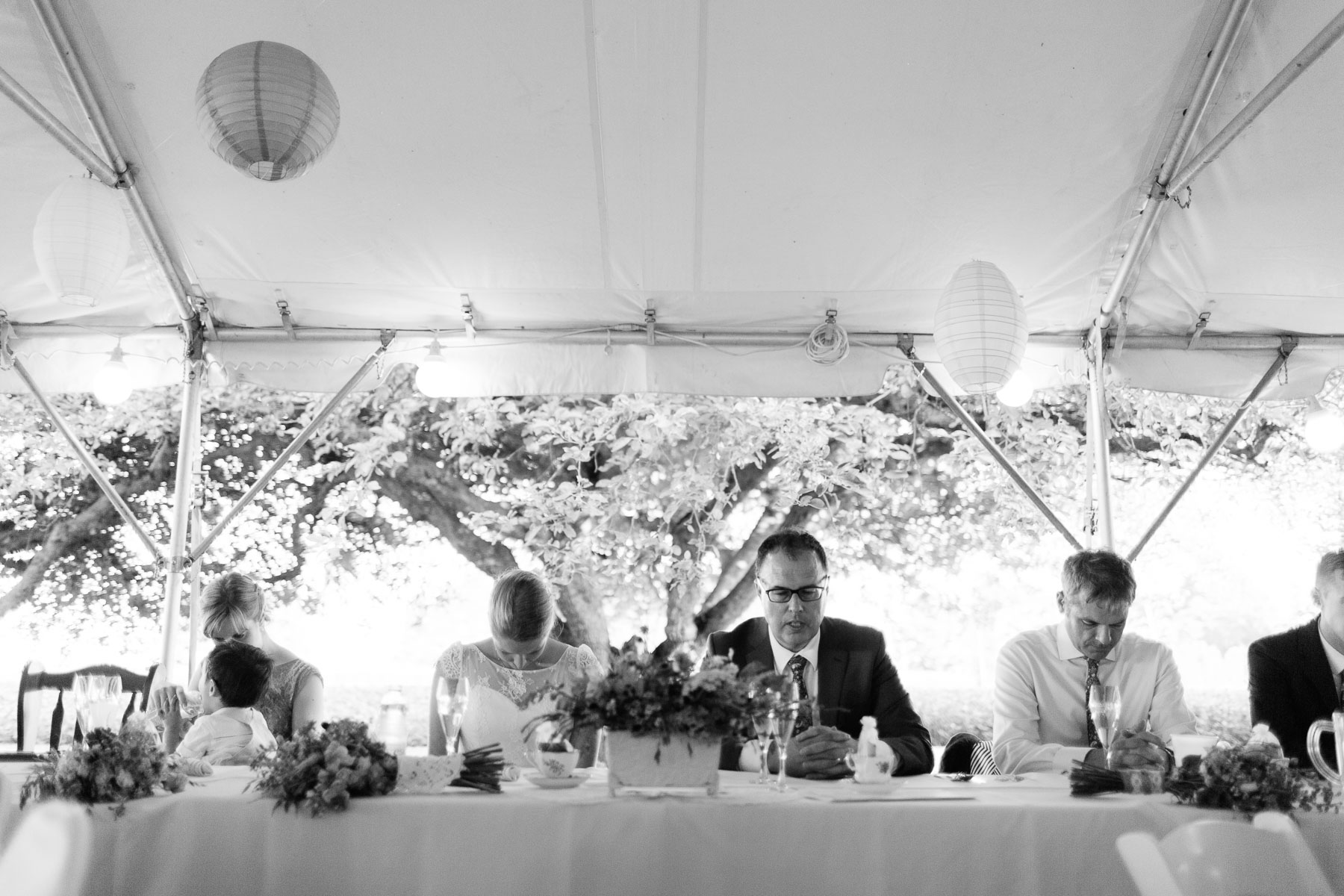 Bride, groom, and wedding party at reception table praying before their meal at this rural farm wedding.