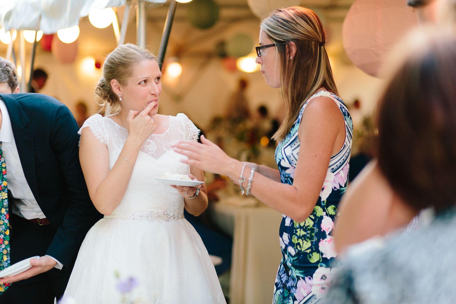 Bride licking fingers and holding pie while talking to guest in this rural family farm wedding.