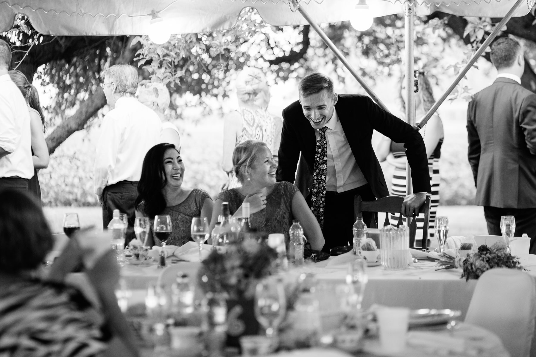 Groomsman laughing with two bridesmaids at the dinner table in this rural farm wedding.