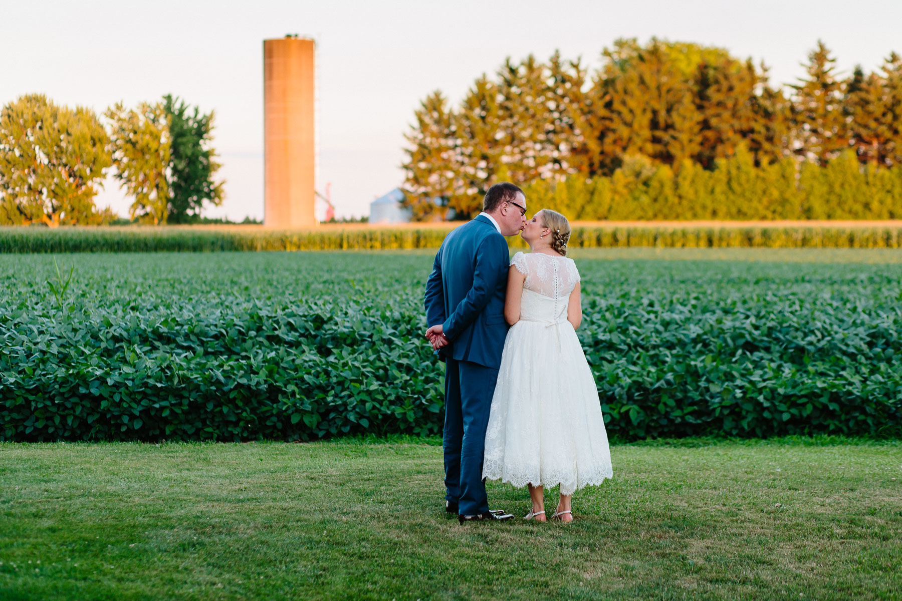 Bride and groom kissing in front of crops and silo in candid moment at a rural farm wedding.