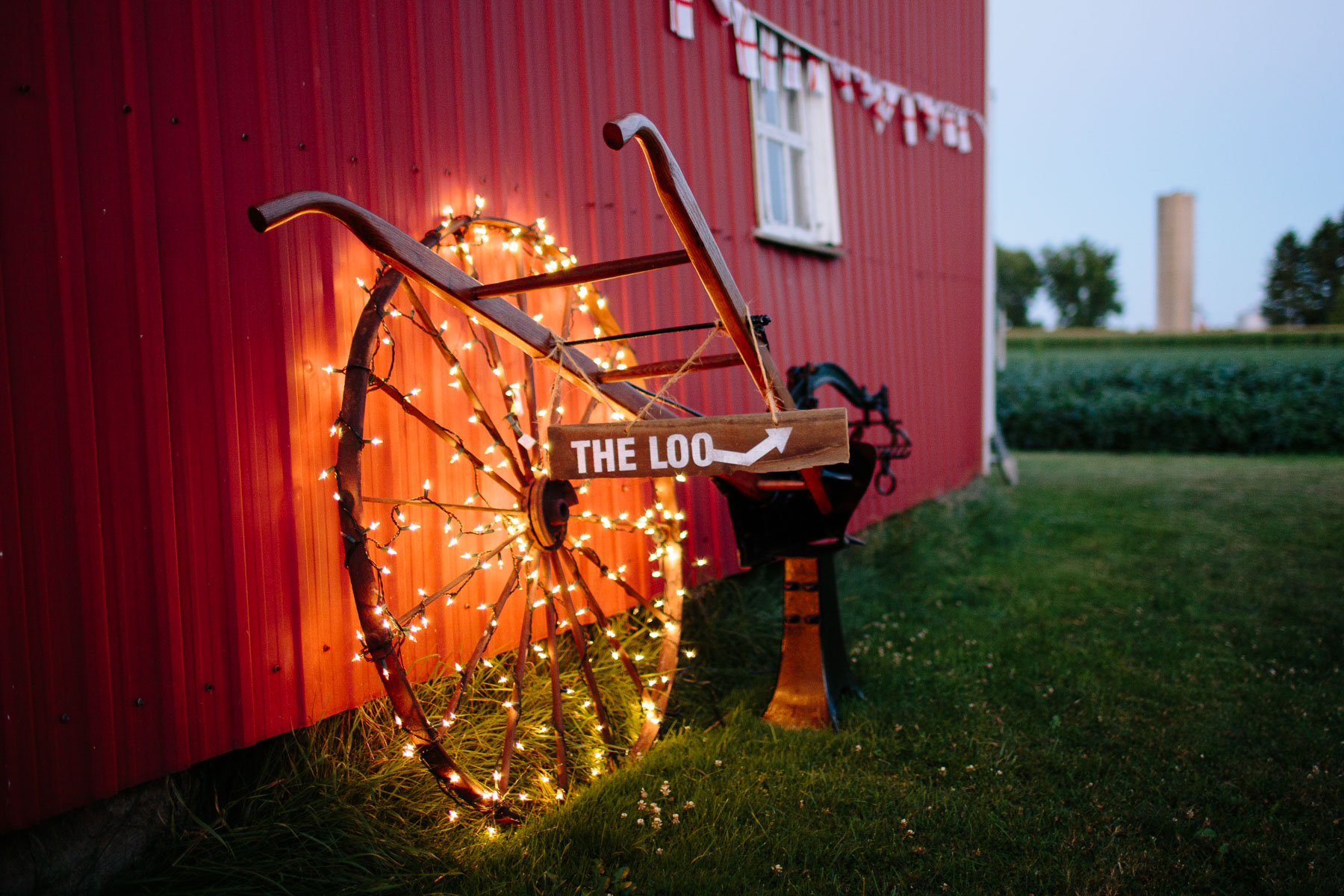 String lights around a rustic wooden wheel leaning on the barn in this rural farm wedding.